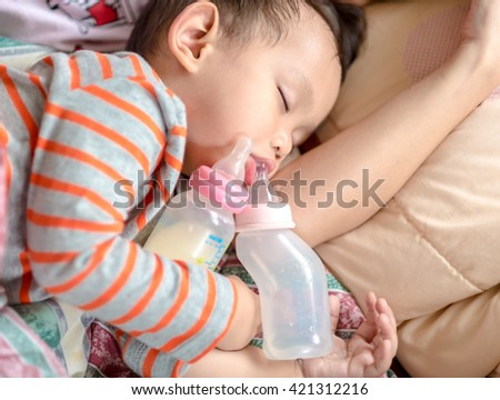 milk bottle and water bottle holding by asian baby boy.  sleeping in mother arm