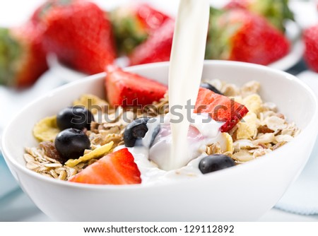 milk pouring into bowl of cereals with fresh berries - stock photo