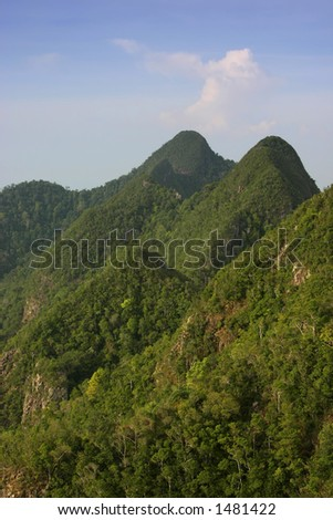 600 million year-old mountains on the tropical island of Langkawi, Malaysia-Vertical Format - stock photo