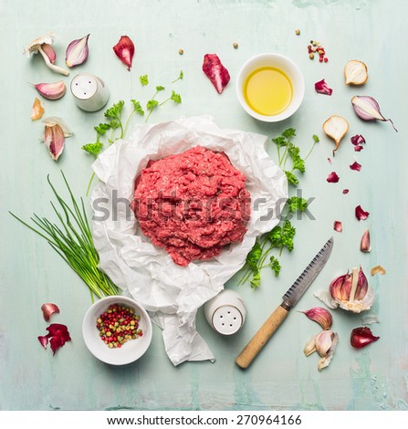 minced meat with cooking ingredients, oil, herbs and spices on blue wooden background , top view - stock photo