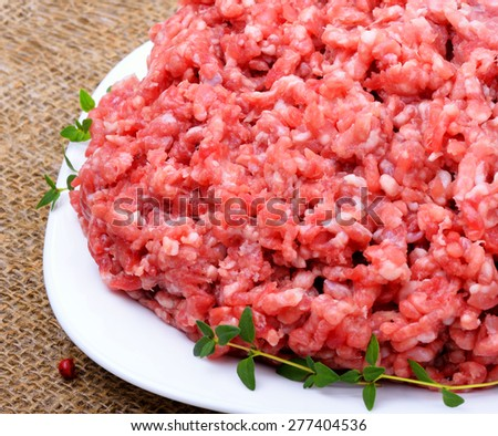 minced meat with pepper, thyme and garlic on sacking background isolated on white - stock photo