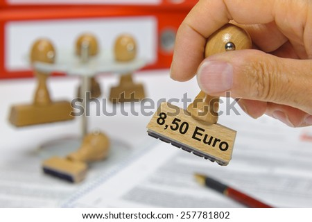 Mindestlohn 8,50 Euros printed on rubber rubber stamp - minimum wage 8,50 Euro - stock photo