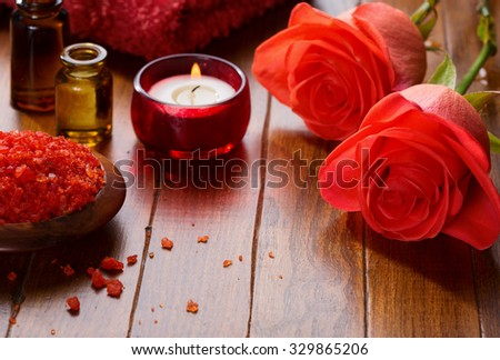 Mineral bath salts, Essential oil, candle and flowers on the brown wooden table. - stock photo