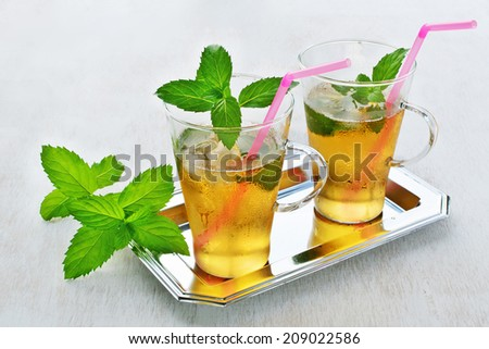 Mint Julep Cocktail in glasses on a tray against a white painted wooden background.