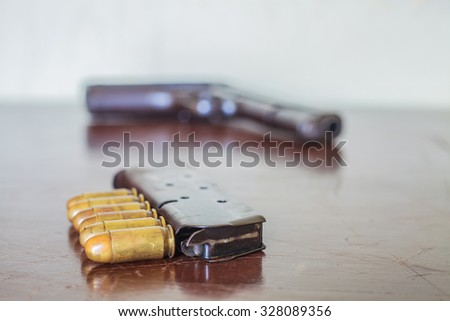 11 mm.  And gun ammunition on wood table. - stock photo