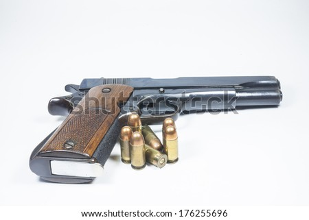 11 mm. Black handgun And ammunition isolated on white