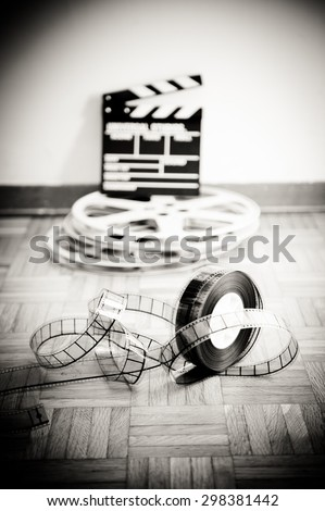35 mm cinema film reel and out of focus movie clapper board in background on wooden floor in vintage black and white vertical frame - stock photo