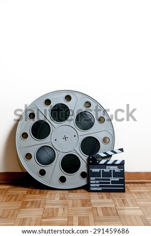 35 mm cinema movie roll with clapper on wooden floor and white wall background vertical frame - stock photo