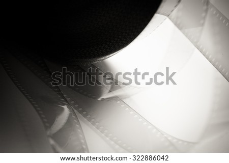 35 mm film detail with movie reel in black and white - stock photo