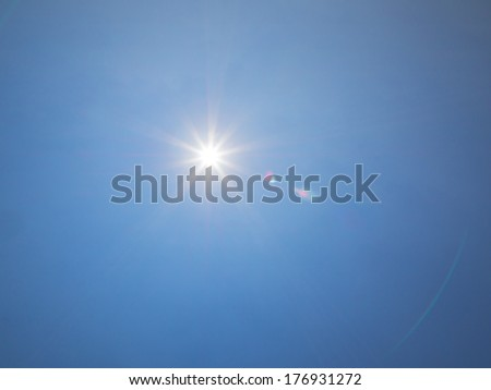 12mm lens flare of the sun on blue sky - stock photo