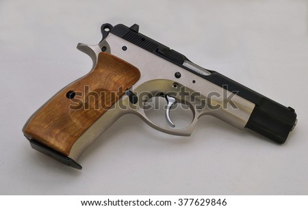 9 mm pistol with wooden handle. - stock photo