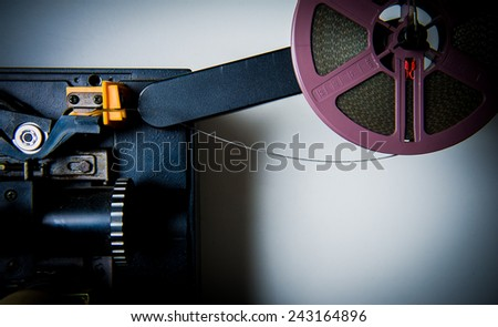 8mm projector body part with film reel, lens and spools, vintage color look - stock photo