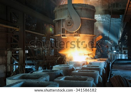 molten metal poured from ladle into mould - stock photo
