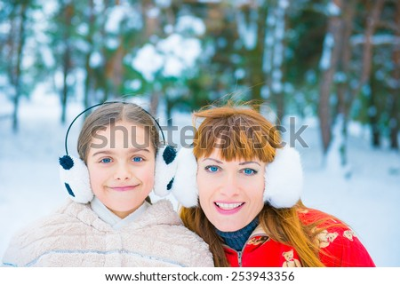Mom and daughter in the park in winter, cheerful two girls in the winter forest, two funny portrait in winter - stock photo