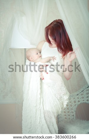 Mom is holding the baby in the open arms on a light background