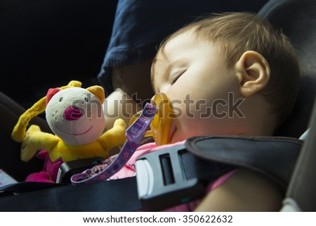 9 month old baby girl sleeping in the car seat with her puppet - stock photo