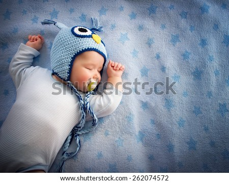 4 month old baby in owl hat sleeping on blue blanket - stock photo
