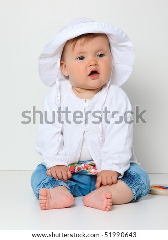 7 month old baby sitting with hat dressed in jeans and jumper