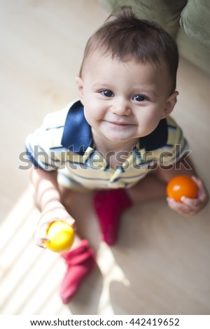 9 month old boy sitting on the floor, looking up at Mommy - stock photo