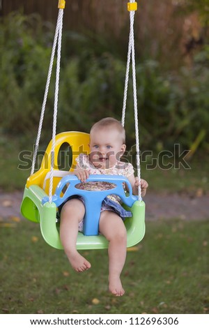 10 month old girl on a garden swing, having fun and laughing. - stock photo