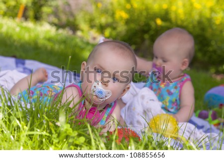 8 month old identical baby twin sisters having fun in the garden. - stock photo