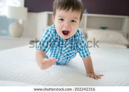 18 month old mixed race Asian boy plays angry in an upmarket bedroom