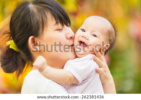 5 months baby feeling happy and smiles with her mother in the garden - stock photo