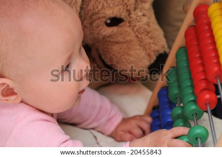 5 months Baby girl playing with multicoloured abacus - stock photo