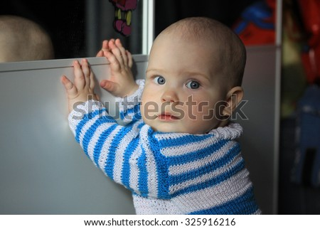 10-months baby standing near a wardrobe with a mirror - stock photo
