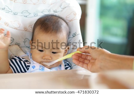 6 months old Asian baby eating food for the first time