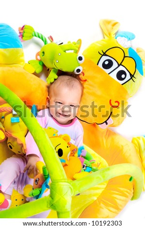 8 months old baby girl enjoy playing with soft baby toys. Studio shot. All toys visible on the photo are officially property released. - stock photo