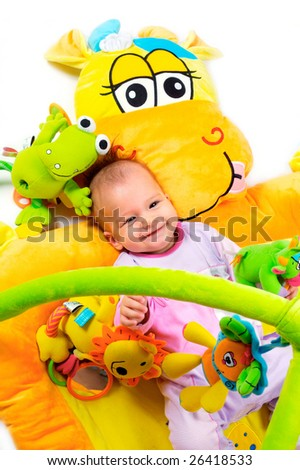 8 months old baby girl enjoy playing with soft baby toys. Studio shot. All toys visible on the photo are officialy property released. - stock photo