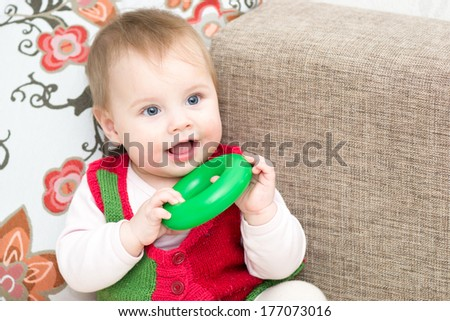 8 months old baby girl playing with pyramid ring - stock photo