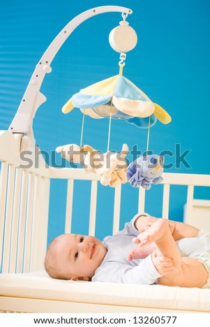 4 months old happy baby boy lying on crib playing with his cute little feet, smiling. Toys are officially property released. - stock photo