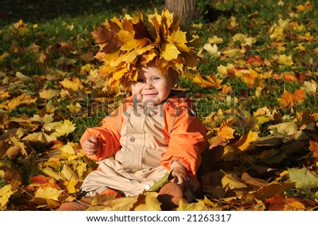 7-months Smiling Baby-girl with maple leaves on head sitting in pile of maple leaves