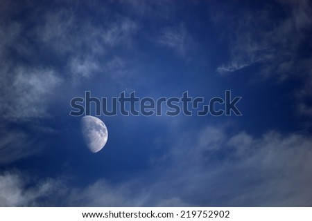 Moon on dark sky with clouds.