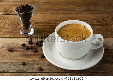 Morning strong coffee cup and coffee beans on rustic background. Coffee break with white mug. - stock photo
