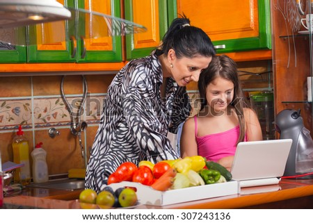Mother and daughter in the kitchen using the laptop. - stock photo