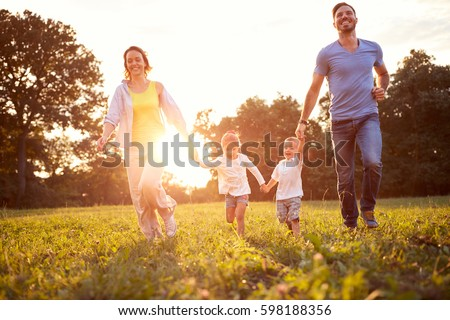 Mother and father with children running in green nature