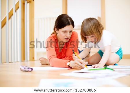 mother and her child sketching on paper at parquet floor. Focus on woman only - stock photo