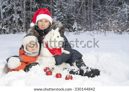 mother and son walking with white Spitz dog outdoors in winter day - stock photo