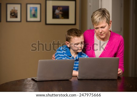 Mother and young son working together on computers.