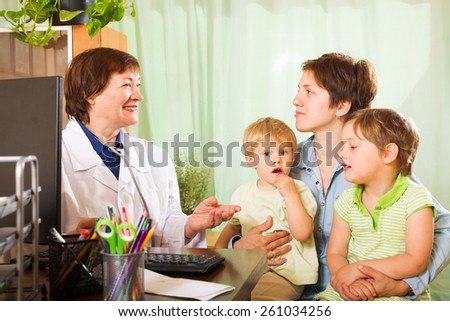mother of two children  talking with friendly pediatrician doctor at clinic office - stock photo