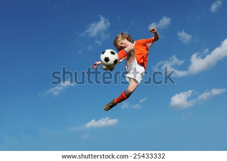 (MOTION BLUR ON FEET AND BALL) young boy, football player doing amazing kick - stock photo
