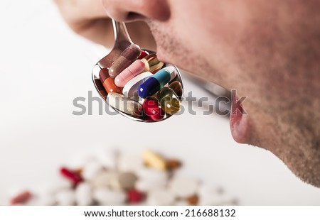 mouth with spoon full of pills - stock photo