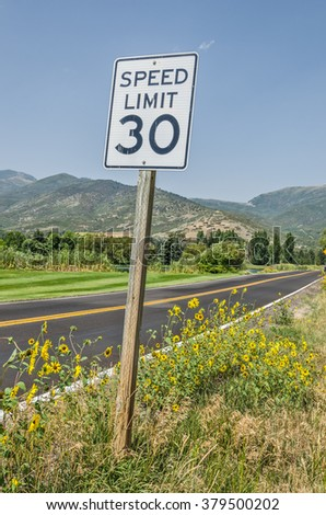 30 mph speed limit sign on a scenic road heading towards the mountains