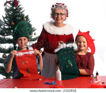 Mrs. Santa Claus with a pair of proud young elves showing off their hand crafted Christmas stockings