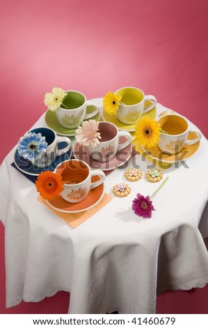 6 multi-coloured cups on a table - stock photo