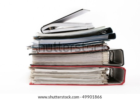 Multicolored pile of binders / files with papers on white background.