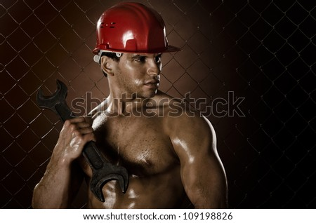 muscular worker man, in  safety helmet  with big wrench  in hands, on netting fence background - stock photo